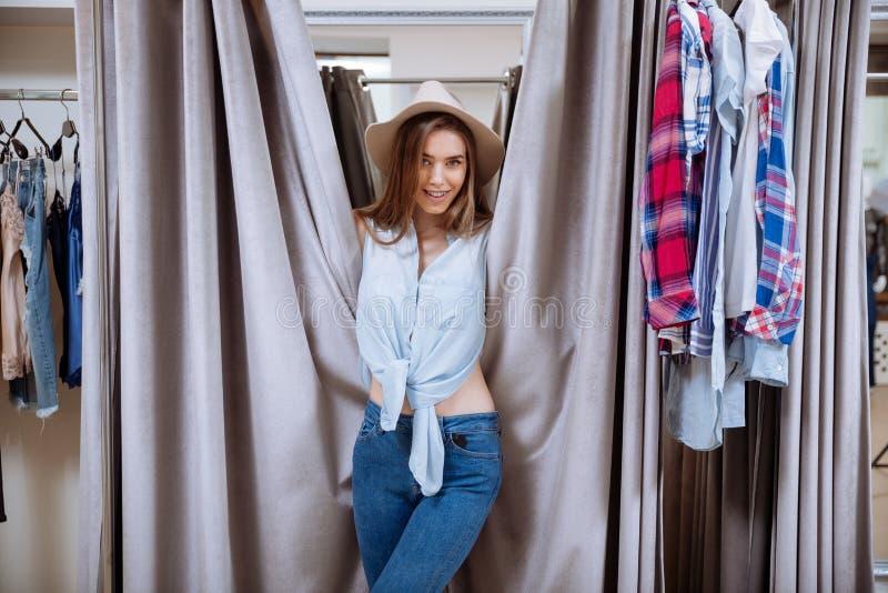 Glimlachende speelse jonge vrouw die zich in kleedkamer bevinden royalty-vrije stock foto