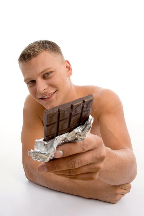 Glimlachende spiermens die chocolade toont royalty-vrije stock fotografie