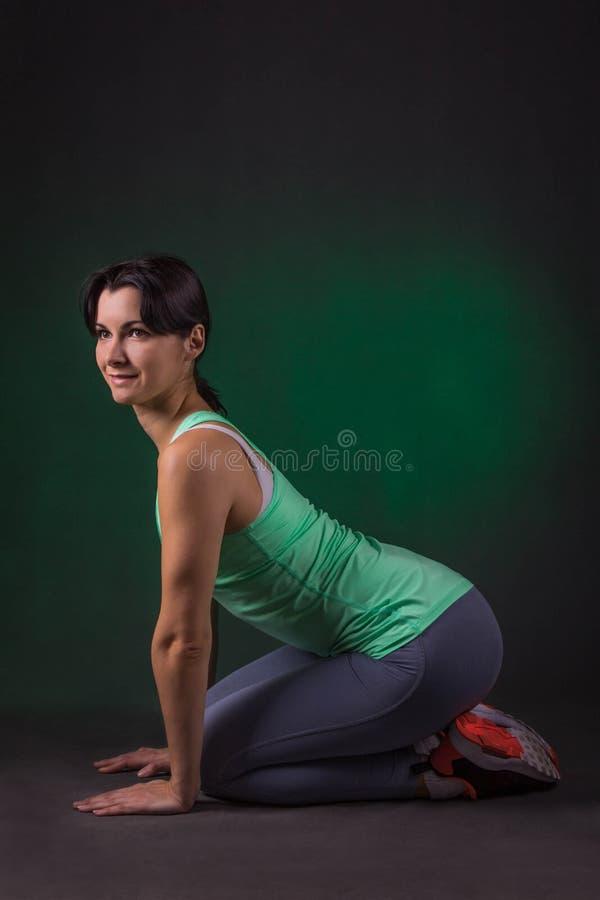 Glimlachende sportieve vrouw, de zitting van de geschiktheidsvrouw op een donkere achtergrond met groene backlight stock afbeeldingen