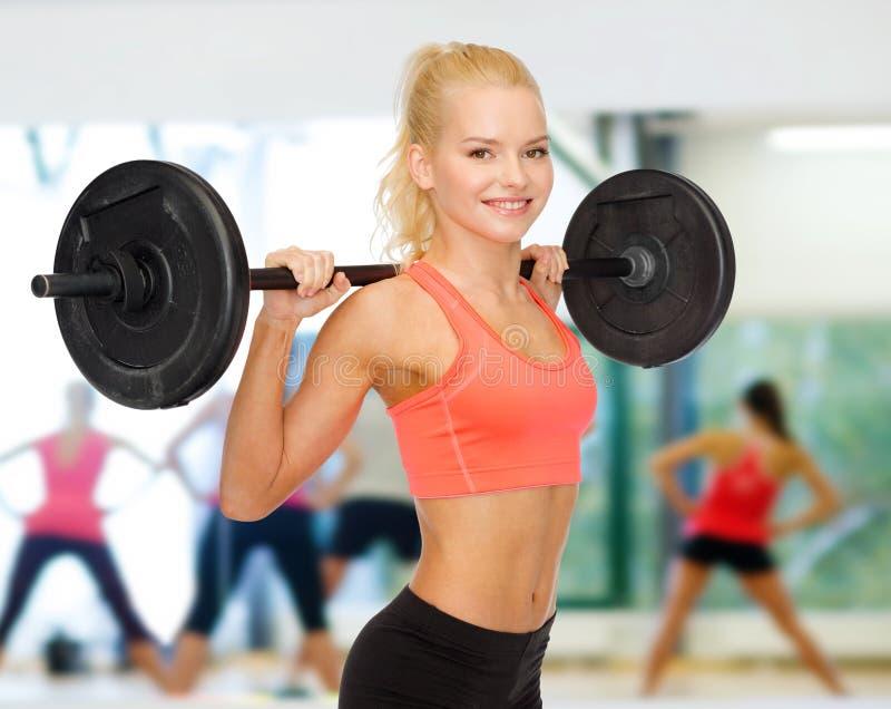 Glimlachende sportieve vrouw die met barbell uitoefenen royalty-vrije stock foto