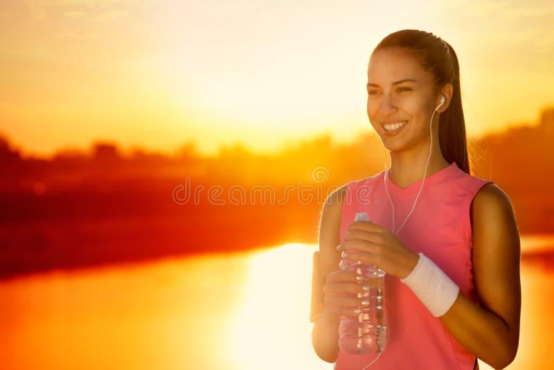 Glimlachende sportieve vrouw met fles water stock foto's