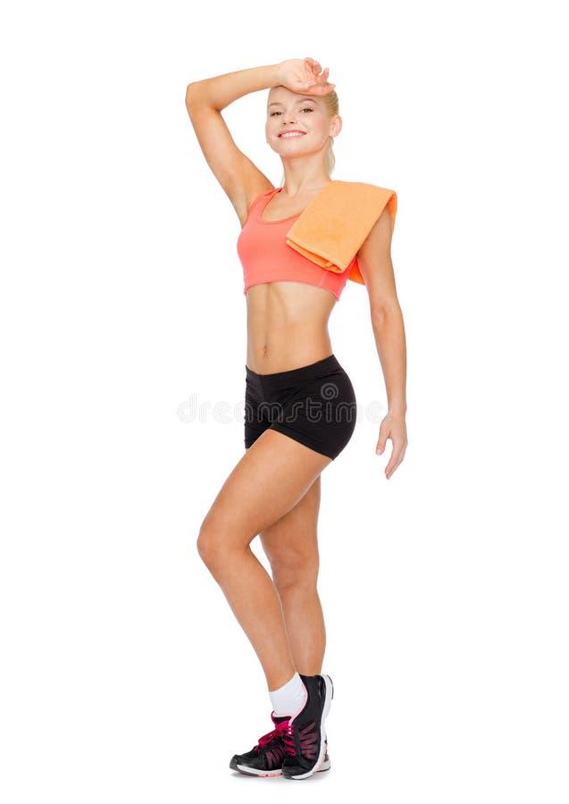Glimlachende sportieve vrouw met handdoek het afvegen van zweet stock fotografie