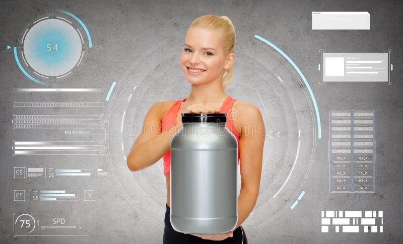 Glimlachende sportieve vrouw met kruik proteïne royalty-vrije stock afbeelding