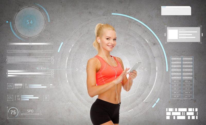 Glimlachende sportieve vrouw met smartphone en oortelefoons royalty-vrije stock fotografie