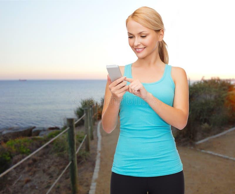 Glimlachende sportieve vrouw met smartphone in openlucht royalty-vrije stock afbeeldingen