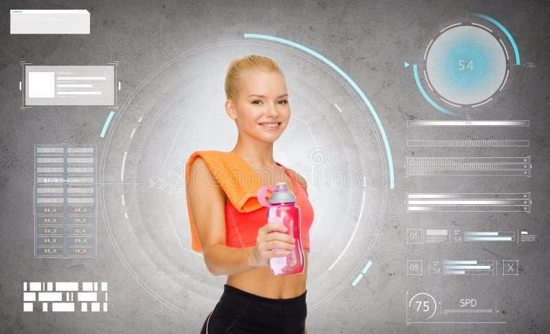 Glimlachende sportieve vrouw met waterfles en handdoek royalty-vrije stock foto's