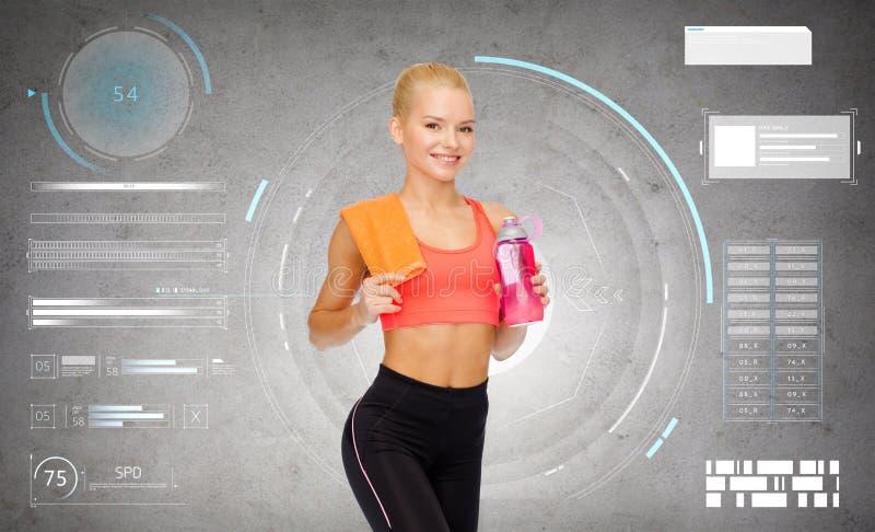 Glimlachende sportieve vrouw met waterfles en handdoek stock foto