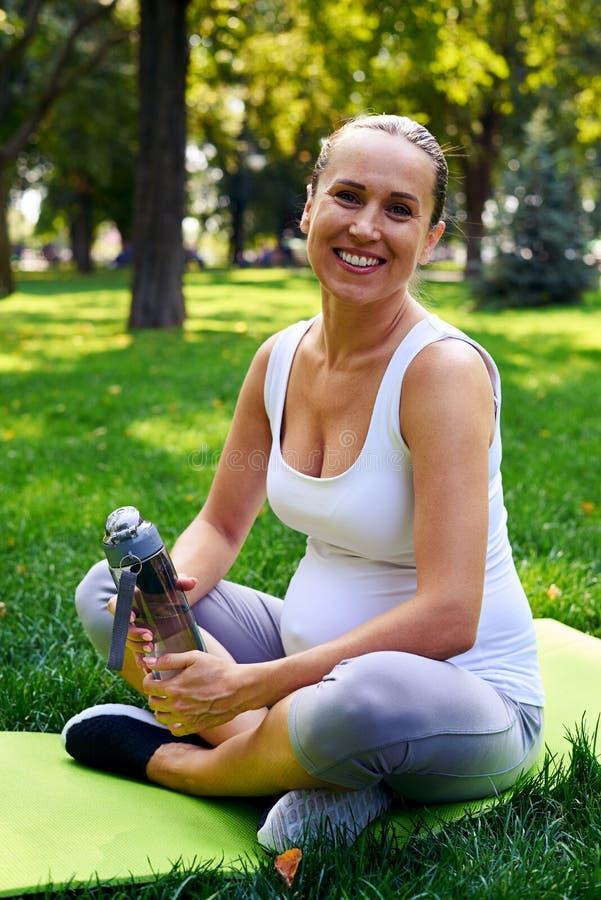 Glimlachende sportieve zwangere vrouw met fles water in park stock afbeelding