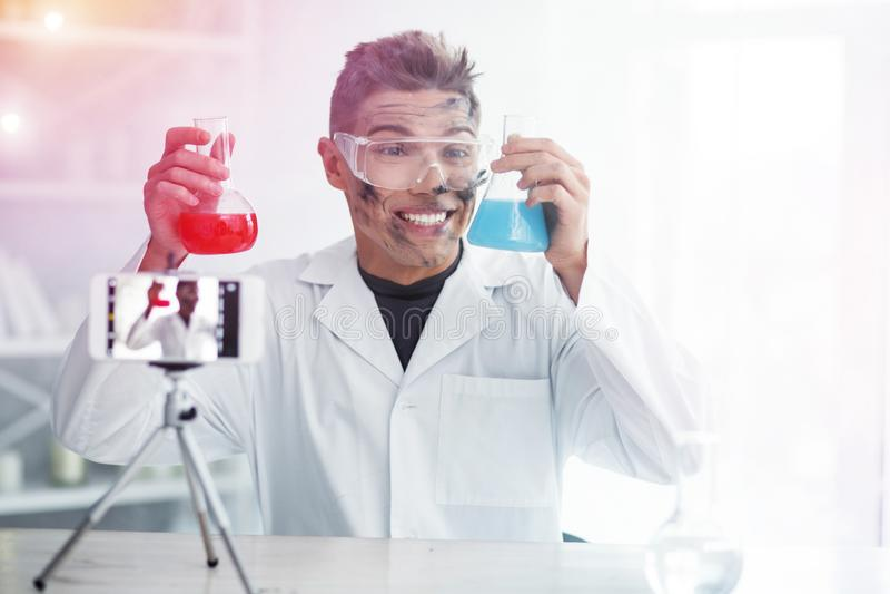 Glimlachende student die vrolijk zelfs daarna niet succesvol chemieexperiment voelen stock afbeelding