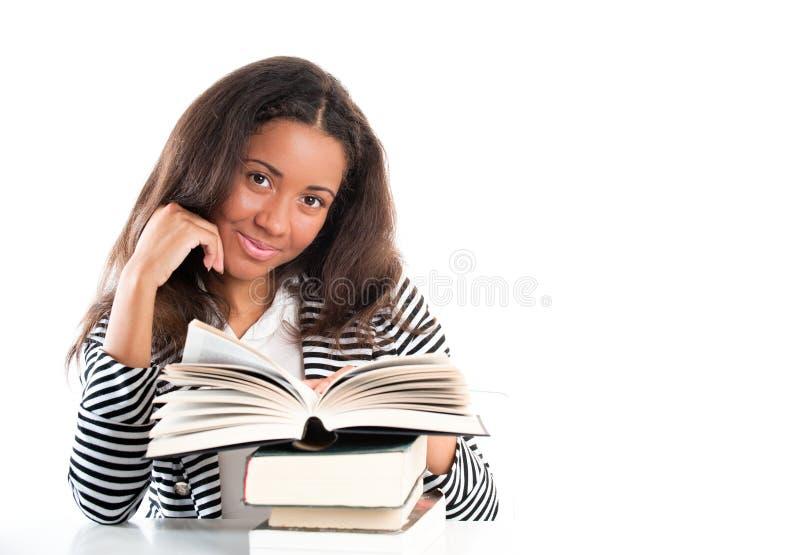Glimlachende student met open boeken die thuiswerk doen stock afbeelding