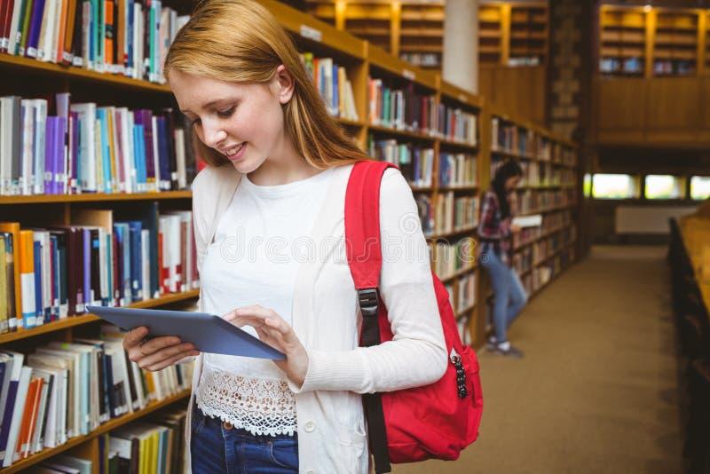 Glimlachende student met rugzak die tablet in bibliotheek gebruiken stock afbeeldingen