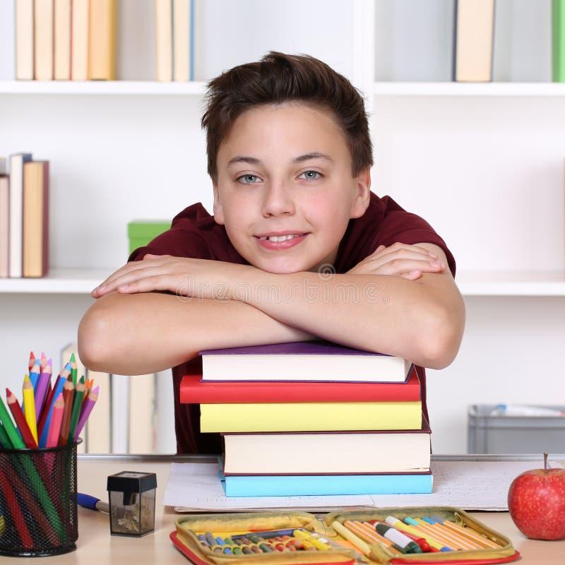 Glimlachende student op een stapel boeken op school royalty-vrije stock afbeeldingen