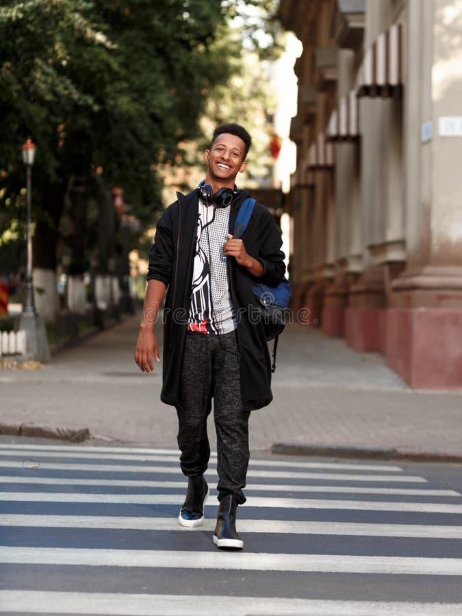 Glimlachende student in vrijetijdskleding die buiten op zebrapad wekken, die camera bekijken, op een straatachtergrond wordt ge?s stock foto's
