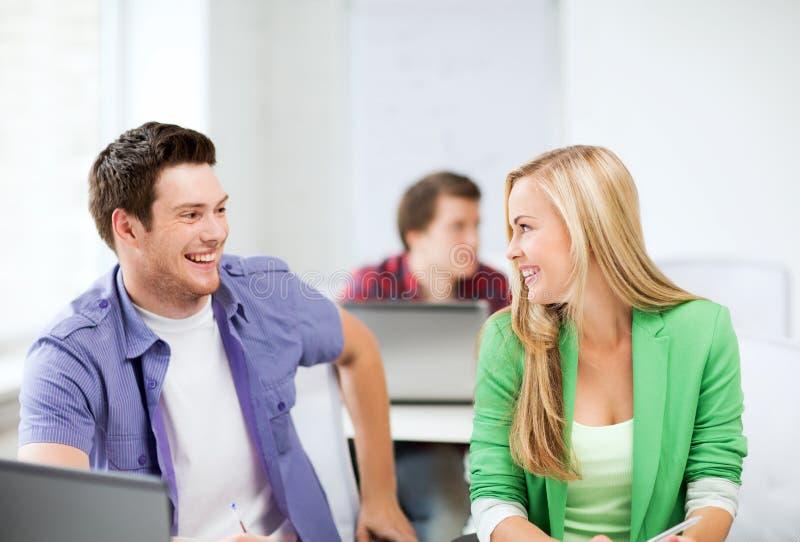 Glimlachende studenten die elkaar op school bekijken royalty-vrije stock afbeeldingen