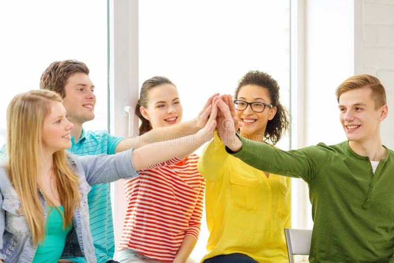 Glimlachende studenten die hoge vijf gebaarzitting maken stock foto