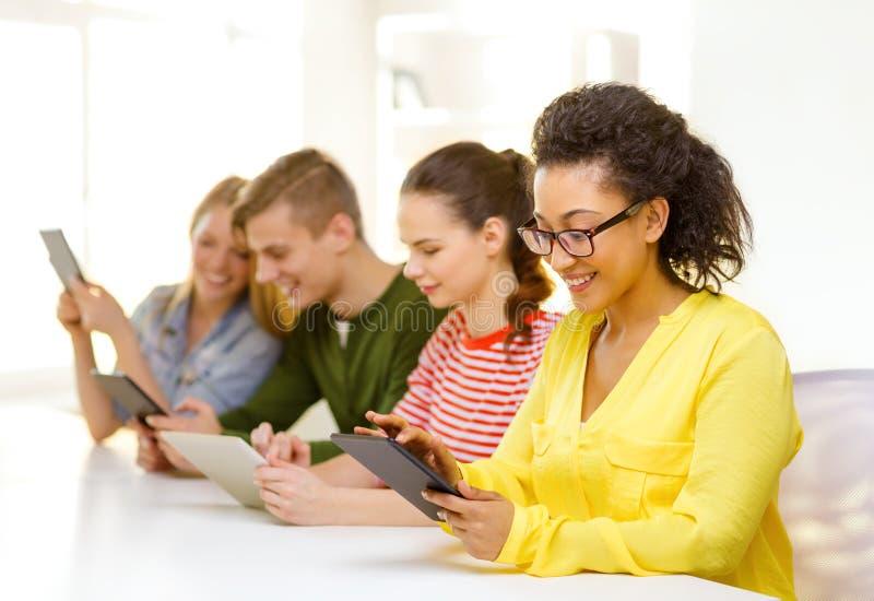 Glimlachende studenten die tabletpc bekijken op school royalty-vrije stock fotografie