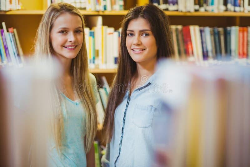 Glimlachende studenten die zich dichtbij boekenrekken verenigen royalty-vrije stock foto