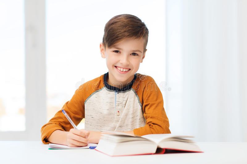 Glimlachende studentenjongen die aan notitieboekje thuis schrijven royalty-vrije stock foto