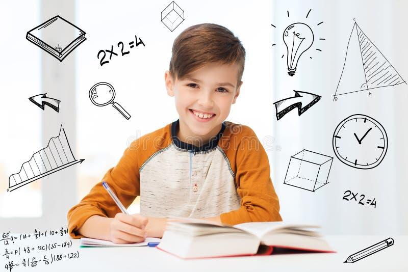 Glimlachende studentenjongen die aan notitieboekje thuis schrijven royalty-vrije stock afbeeldingen