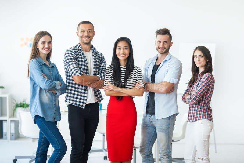 Glimlachende succesvolle groep bedrijfsmensen met gekruiste wapens stock afbeelding