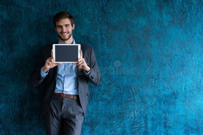 Glimlachende succesvolle jonge zakenman op blauwe achtergrond in een klassiek grijs kostuum die een tablet voorstellen royalty-vrije stock afbeeldingen