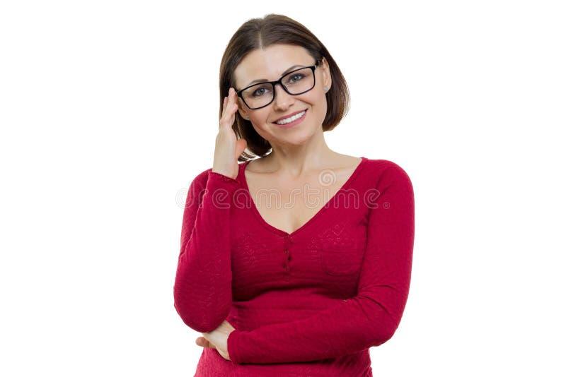 Glimlachende succesvolle zekere vrouw die op middelbare leeftijd in glazen camera op witte geïsoleerde achtergrond bekijken, royalty-vrije stock afbeelding