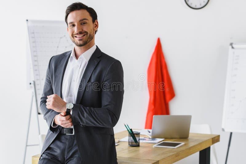 glimlachende super zakenman die zich dichtbij lijst bevinden en camera bekijken stock foto's