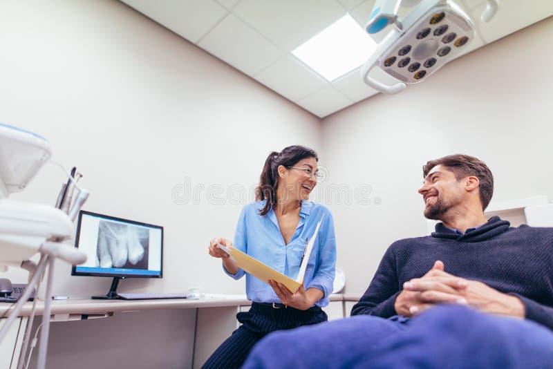 Glimlachende tandarts en patiënt bij tandkliniek stock foto