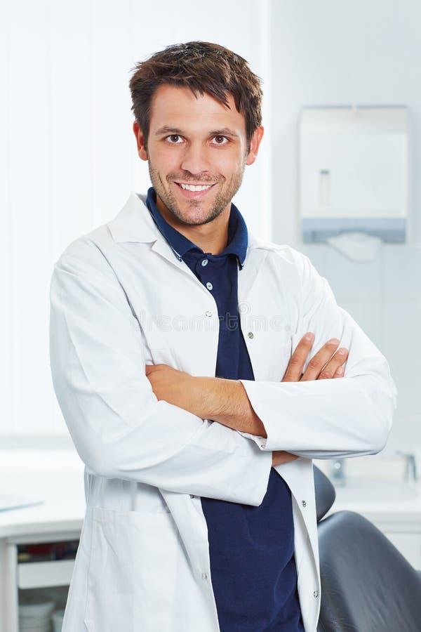 Glimlachende tandarts met gekruiste wapens royalty-vrije stock foto