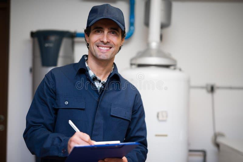 Glimlachende technicus die een warm waterverwarmer onderhouden royalty-vrije stock afbeeldingen