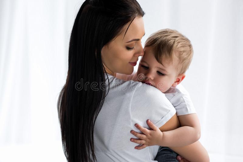 glimlachende tedere moeder die leuke babyjongen houden royalty-vrije stock foto
