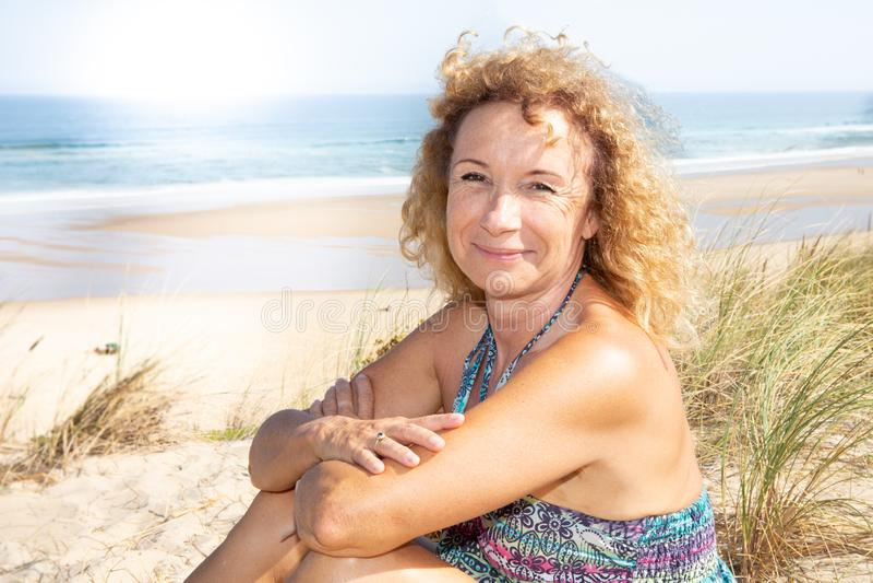 Glimlachende teruggetrokken hogere blondevrouw in het strand van het randduin in de zomer royalty-vrije stock foto's