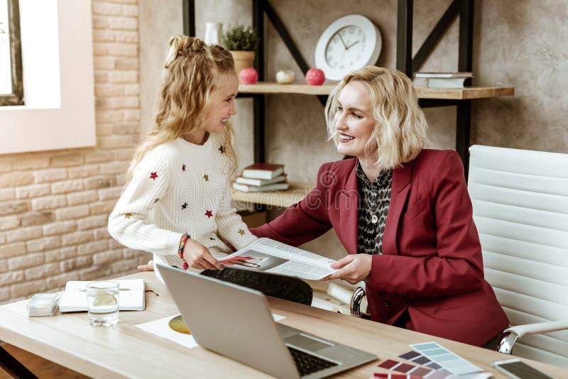 Glimlachende tevreden blondemoeder die pret met haar positieve dochter hebben op het werk stock afbeelding
