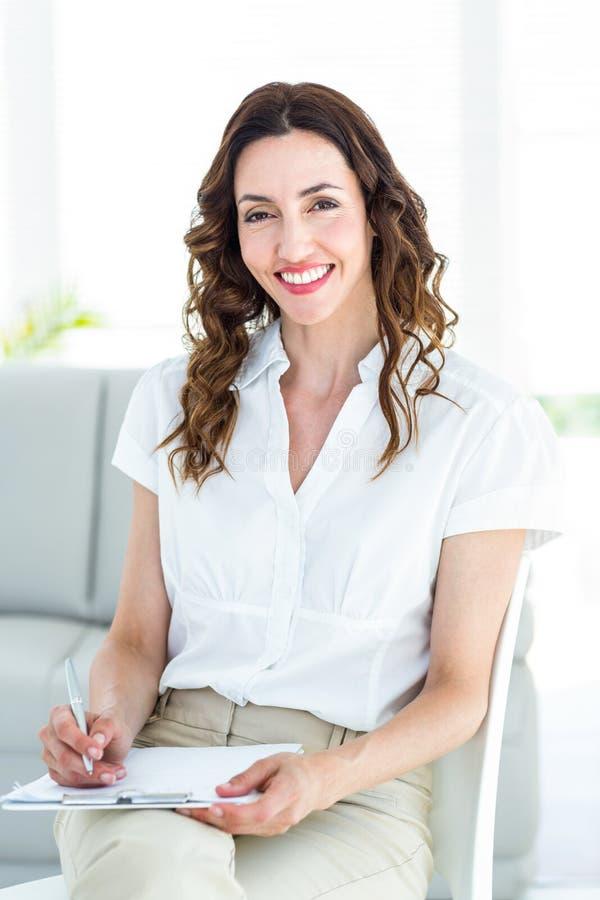 Glimlachende therapeut die nota's nemen royalty-vrije stock afbeelding