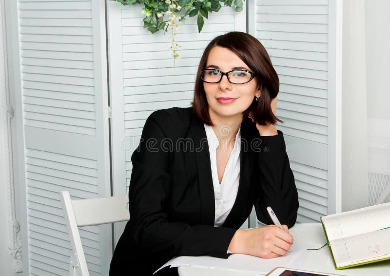 Glimlachende therapeut die nota's over witte achtergrond nemen stock afbeelding