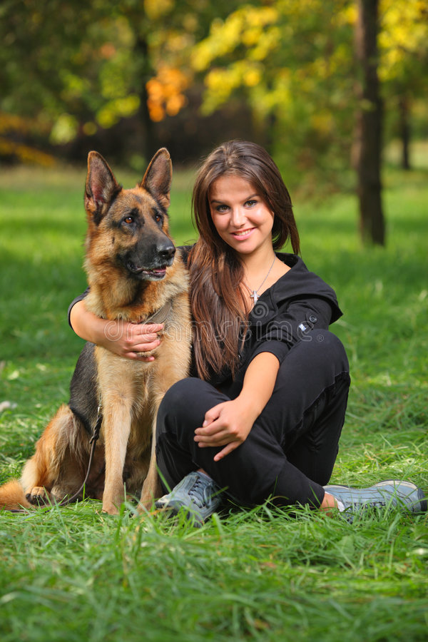 Glimlachende tiener die een hond koestert stock afbeelding