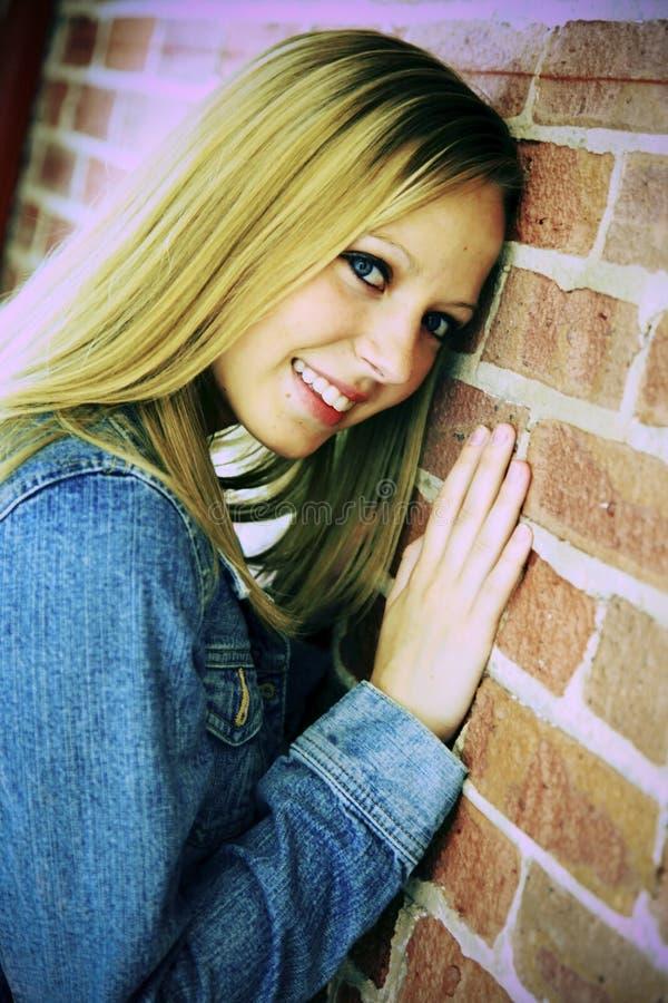 Glimlachende tiener die op muur leunt royalty-vrije stock afbeelding