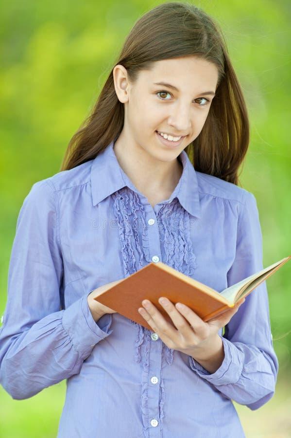 Glimlachende tiener die oranje boek lezen stock foto's