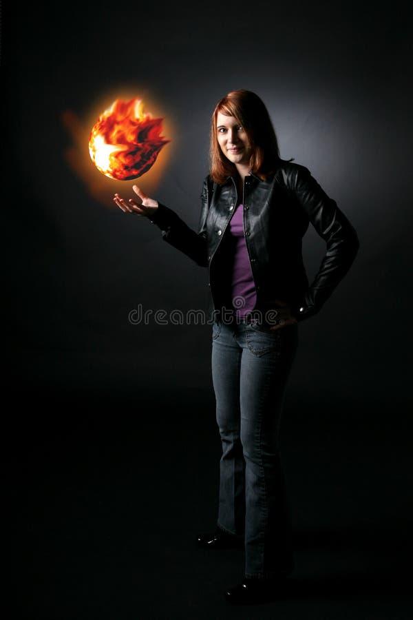 Glimlachende tiener die oranje vuurbol houdt stock afbeeldingen