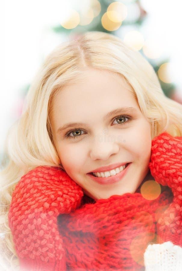 Glimlachende tiener in rode vuisthandschoenen en sjaal stock foto