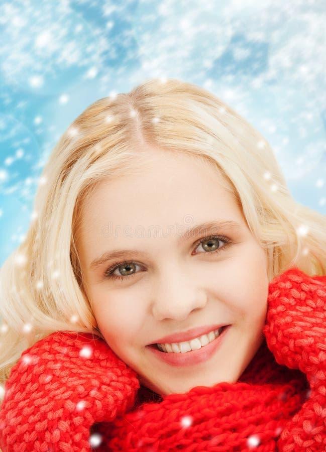 Glimlachende tiener in rode vuisthandschoenen en sjaal stock foto's