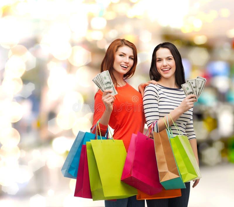 Glimlachende tieners met het winkelen zakken en geld stock foto's