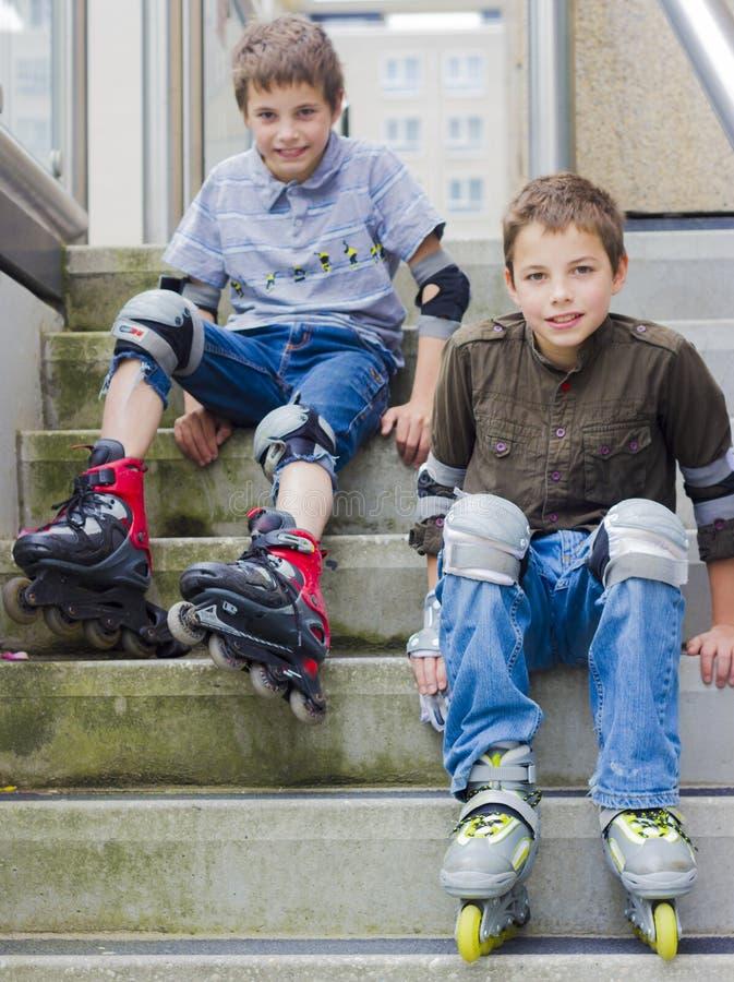 Glimlachende tieners in rol-blading beschermingsuitrustingen royalty-vrije stock afbeelding