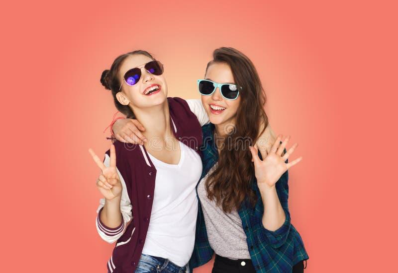 Glimlachende tieners in zonnebril die vrede tonen stock foto's