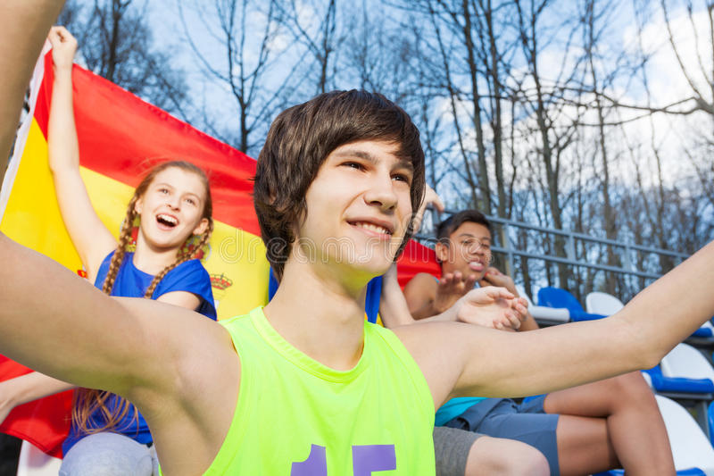 Glimlachende tienersportverdedigers die op het spel letten stock afbeelding