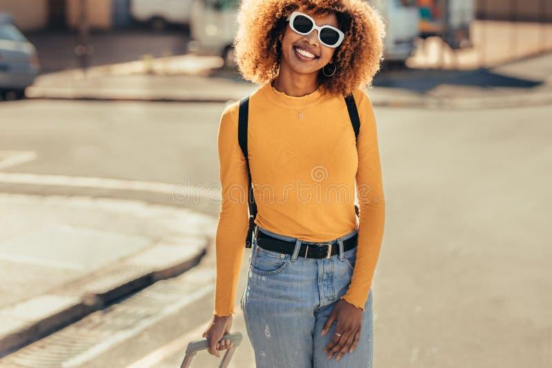 Glimlachende toeristenvrouw die op straat lopen stock afbeeldingen