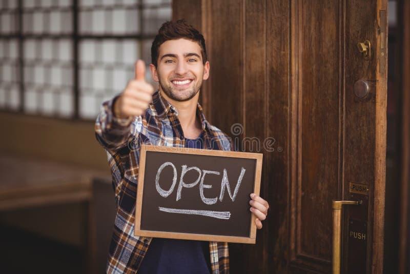Glimlachende toevallige kelner die bord en duimen tonen stock foto's