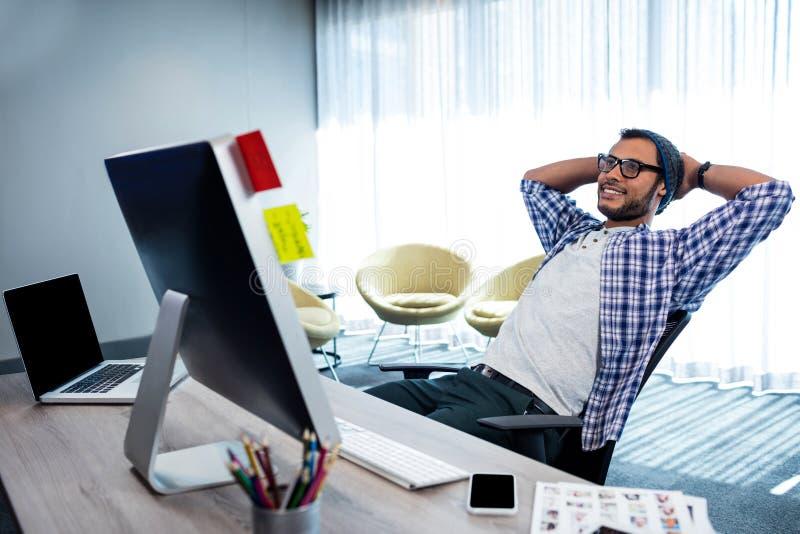 Glimlachende toevallige mens met handen achter hand die bij bureau rusten stock foto's
