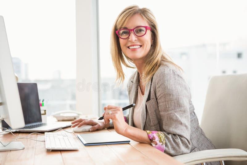 Glimlachende toevallige ontwerper die computer en becijferaar met behulp van royalty-vrije stock afbeeldingen