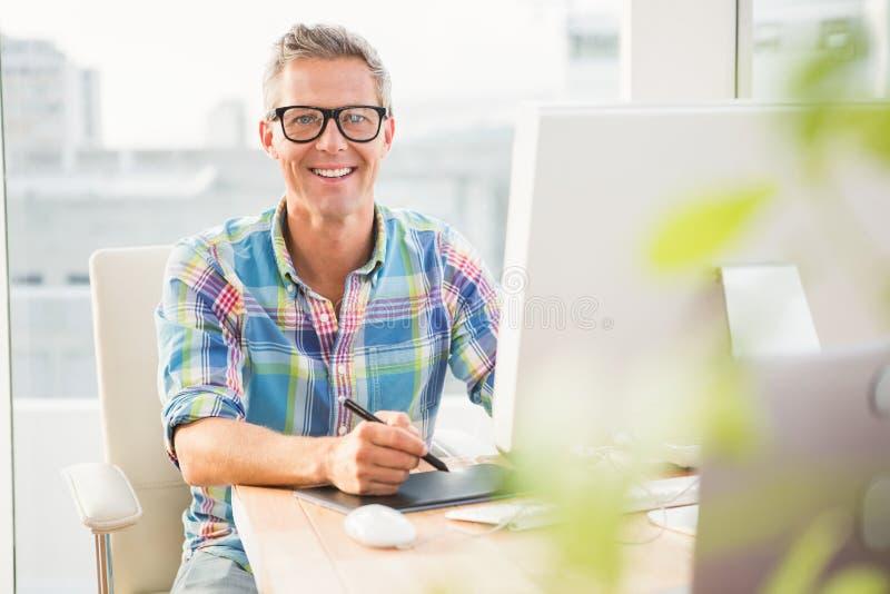 Glimlachende toevallige ontwerper die met becijferaar werken royalty-vrije stock afbeelding